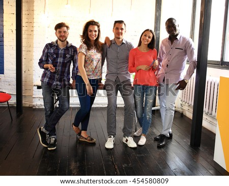 Portrait of happy young people in a meeting looking at camera and smiling. Young designers working together on a creative project. - stock photo