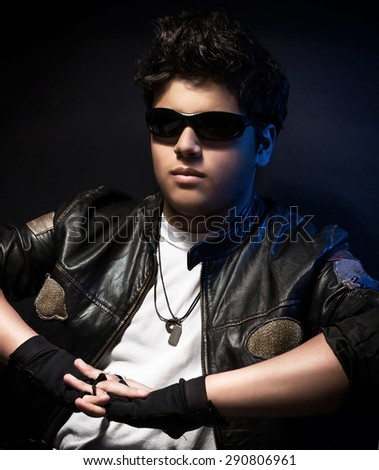 Portrait of happy young stylish biker over dark blue background, wearing fashionable sunglasses and leather jacket, fashion for motorcyclists