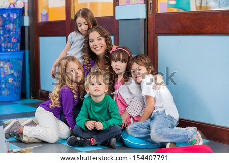 Portrait of happy young teacher and students sitting together on floor in kindergarten - stock photo