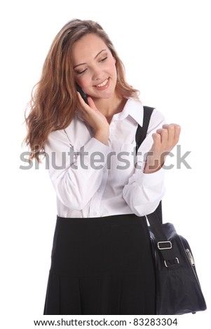 Portrait of happy young teenage school girl, deep in conversation on her cell phone. She is wearing black and white school uniform. - stock photo