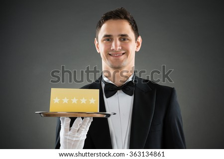 Portrait of happy young waiter holding tray with star rating label against gray background - stock photo