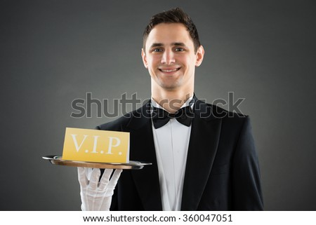 Portrait of happy young waiter holding tray with VIP sign against gray background - stock photo
