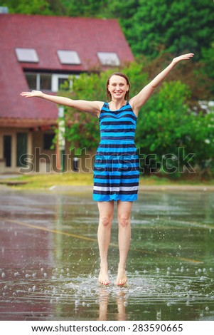 Portrait of happy young white Caucasian  girl in blue dress jumping in puddles during the rain thunderstorm on a bright summer day outside, sports recreation leisure activity and freedom concept  - stock photo