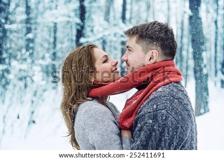 Portrait of happy young woman and her boyfriend in winter park - stock photo