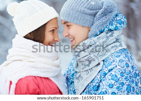 Portrait of happy young woman and her boyfriend in winterwear looking at one another  - stock photo