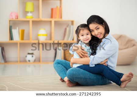 Portrait of happy young woman and her daughter hugging and looking at the camera - stock photo