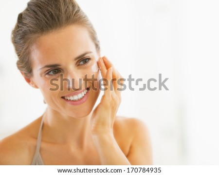Portrait of happy young woman applying cream in bathroom - stock photo
