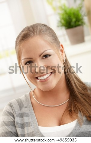Portrait of happy young woman at home, looking at camera, smiling.
