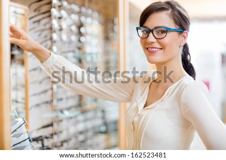 Portrait of happy young woman buying new glasses at optician store - stock photo