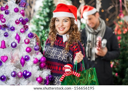 Portrait of happy young woman carrying shopping bag at Christmas store with man in background - stock photo
