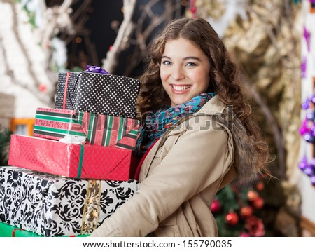 Portrait of happy young woman carrying stacked Christmas gifts in store - stock photo