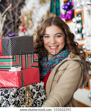 Portrait of happy young woman carrying stacked Christmas presents in store - stock photo