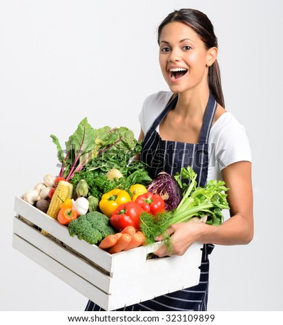Portrait of happy young woman chef holding a crate full of fresh organic vegetables on grey background, promoting eating seasonally and sourcing from local producers