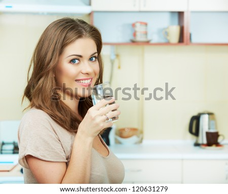 Portrait of happy  young woman drinking water against kitchen background. - stock photo