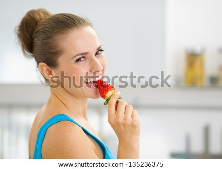 Portrait of happy young woman eating strawberry - stock photo