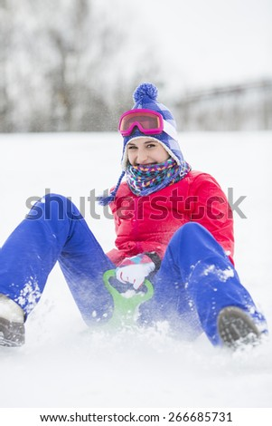 Portrait of happy young woman enjoying sled ride in snow - stock photo