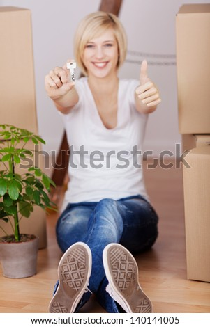 Portrait of happy young woman gesturing thumbs up and holding key while sitting on hardwood floor - stock photo