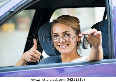 Portrait of happy young woman gesturing thumbs up while holding key in car - stock photo
