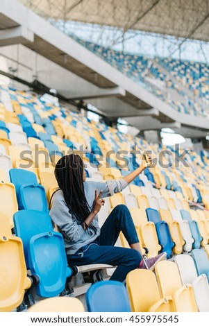 Portrait of happy young woman gesturing victory or peace hand sign taking a selfie with her cellphone at stadium - stock photo