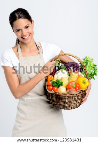 Portrait of happy young woman holding a basket full of fresh organic vegetables on grey background, promoting healthy diet and lifestyle - stock photo