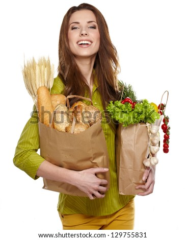 Portrait of happy young woman holding a shopping bag full of groceries on white background - stock photo