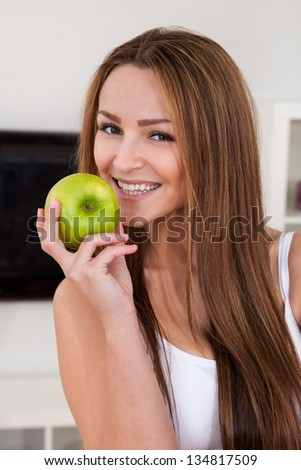 Portrait Of Happy Young Woman Holding Green Apple - stock photo