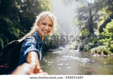 Portrait of happy young woman holding hand of her boyfriend while walking by mountain stream. Couple enjoying a hike in nature. - stock photo