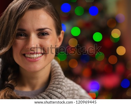 Portrait of happy young woman in front of Christmas lights - stock photo