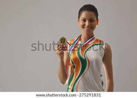 Portrait of happy young woman in sports wear showing gold medal isolated over gray background - stock photo