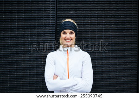 Portrait of happy young woman in sportswear looking at camera smiling. Fitness female against dark wall. - stock photo