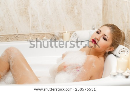 Portrait of happy young woman laying in foam in bathtub. Beautiful woman relaxing in bathtub. beautiful young woman takes bubble bath.