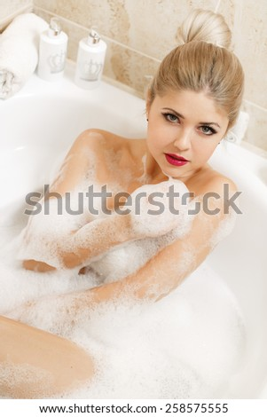 Portrait of happy young woman laying in foam in bathtub. Beautiful woman relaxing in bathtub. beautiful young woman takes bubble bath.  - stock photo