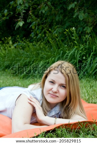 Portrait of happy young woman lying in summer field with green grass.