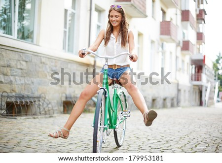 Portrait of happy young woman on bicycle  - stock photo