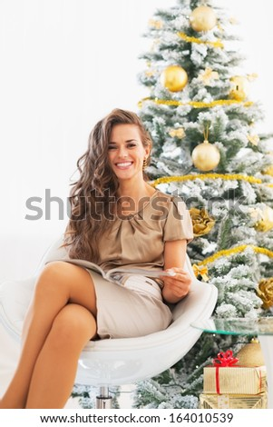 Portrait of happy young woman reading magazine near christmas tree - stock photo