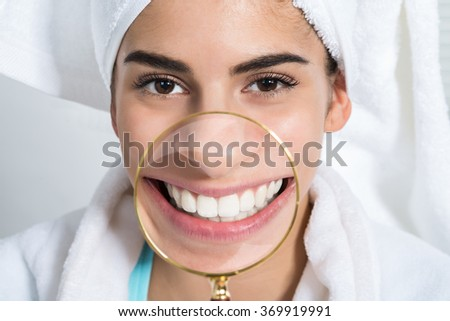 Portrait of happy young woman showing healthy white teeth through magnifying glass at home - stock photo