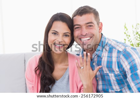 Portrait of happy young woman showing ring while sitting with man at home - stock photo