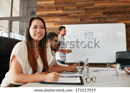 Portrait of happy young woman sitting at conference table with colleagues in background. Asian woman looking at camera smiling while sitting in a business presentation. - stock photo