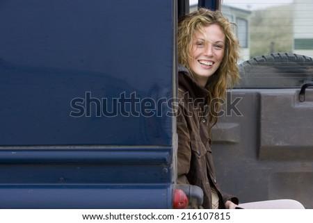 Portrait of happy young woman sitting in van - stock photo