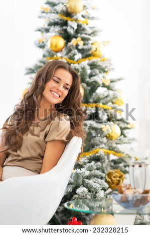 Portrait of happy young woman sitting near christmas tree - stock photo