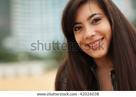 Portrait of happy young woman smiling, looking at camera. Close-up, shallow DOF. - stock photo