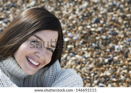 Portrait of happy young woman smiling while sitting at beach - stock photo