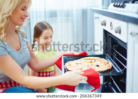 Portrait of happy young woman taking pizza out of oven, her daughter standing near by - stock photo