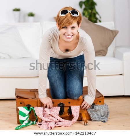 Portrait of happy young woman trying to close her suitcase at home - stock photo