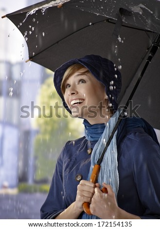 Portrait of happy young woman under umbrella in the rain, smiling. - stock photo