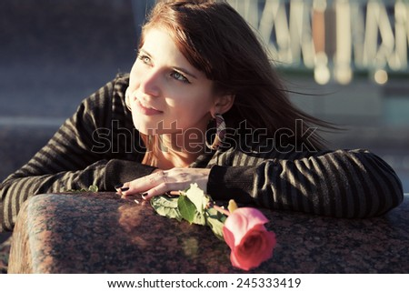 Portrait of happy young woman with a red rose outdoor  - stock photo