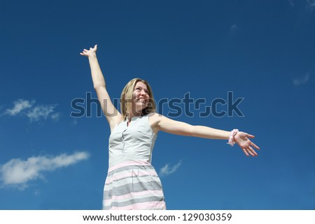 Portrait of happy young woman with arms raised