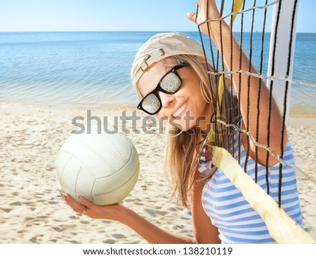 Portrait of happy young woman with ball on sea beach - stock photo
