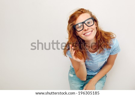 Portrait of happy Young woman with black glasses standing against wall. - stock photo