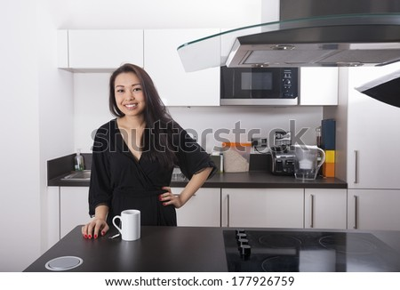 Portrait of happy young woman with coffee mug in kitchen